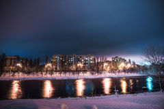 De rivier en de huizen met meerdere verdiepingen bij sneeuwnacht Stock Fotografie