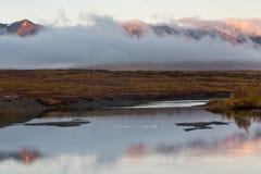 De rivier en de wolk bij de voet bergen stock foto's