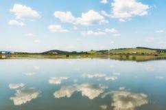 De rivier, het kleine dorp achter het en de blauwe hemel met wolken, ref Royalty-vrije Stock Foto's