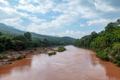De rivier met rood van de zware regen die van de bergen stromen stock fotografie