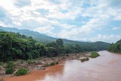 De rivier met rood van de zware regen die van de bergen stromen stock foto's
