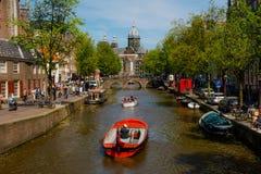De Rivier van Amsterdam en een boot stock afbeeldingen
