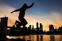 De Rivier van het oosten en de Brugschemer van Brooklyn met mens het springen stock foto
