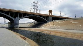 De rivier van Los Angeles met brug en donkere hemel op de achtergrond Stock Foto