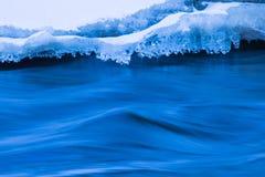 De rivierkust met de sneeuw en het ijs in de zonnige de winterdag royalty-vrije stock afbeelding