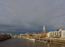 De rivieroevermening van Bremen, Duitsland met vastgelegde schepen en donkere regen betrekt op de achtergrond Stock Fotografie