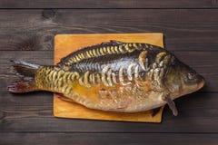 De riviervissen van de spiegelkarper op donkere houten lijst Royalty-vrije Stock Foto's