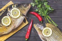 De riviervissen van spiegelkarpers met citroen, kruiden en peper op donkere houten lijst Stock Foto's