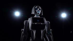 De robot bevindt zich en kijkt recht Zwarte achtergrond stock videobeelden