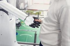 De robot geeft een hand aan een jongen de handen van robotschokken met een mens Stock Fotografie