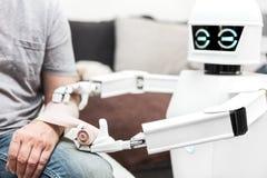 De robot zet een verband op een wapen van een mannelijke patiënt stock foto's