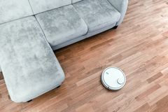 De robotachtige stofzuiger op gelamineerde vloer dichtbij bankclose-up, het slimme huisrobotica draadloze schoonmaken voor vereen royalty-vrije stock fotografie