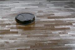 De robotachtige stofzuiger op gelamineerde vloer, het slimme huisrobotica draadloze schoonmaken voor vereenvoudigt routinehuishou royalty-vrije stock foto's