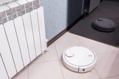 De robotachtige stofzuiger op gelamineerde vloer wordt weerspiegeld in spiegel van koelkast, slimme huisrobotica het draadloze sc stock fotografie