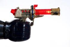 De robothand die van het stuk speelgoed een verlichtingskanon houdt stock foto
