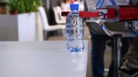 De robothand houdt een fles water media Technologische vooruitgang Het robotachtige wapen houdt een waterfles stock footage