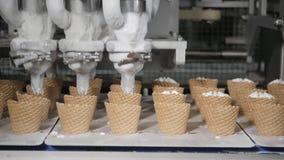 De robotmachine giet automatisch roomijs in een Wafeltje tot een kom vormt De transportband automatische lijnen voor de productie stock video
