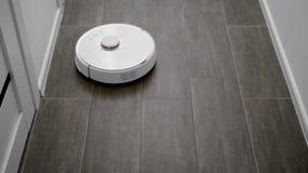 De robotreinigingsmachine beweegt zich over vloer in een moderne flat, die op wijze zonder chauffeur werken, autonoom schoonmaken stock footage