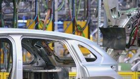 De robots lassen een autolichaam stock videobeelden