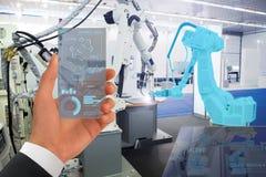 De robots van ingenieurscontroles in een slimme fabriek stock afbeeldingen