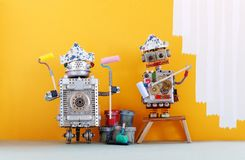De robots van de schildersdecorateur klaar voor binnenlandse verbetering Grappige robotachtige arbeiders met gele verfrollen en e stock fotografie