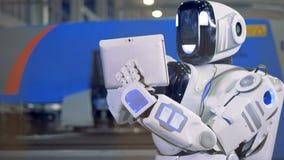 De robotwerken met een tablet, sluiten omhoog Een cyborg typt op een tablet met zijn vingers