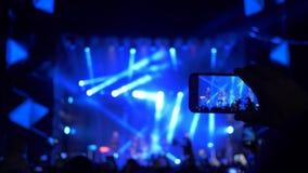 De rockgebeurtenis, menigteventilators met smartphone in handen neemt genoegen levend vermaak en maakt video voor geheugen bij stock videobeelden