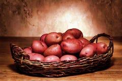 De rode Aardappels van de Huid in Rieten Mand stock foto