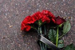 De rode anjersbloemen en namen gezien op de herdenkingssteen toe royalty-vrije stock foto's