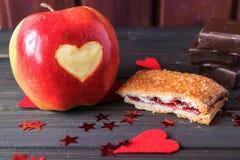De rode appel met gesneden die hart, kersenpastei en chocoladerepen met weinig rood wordt verfraaid speelt de Dag van StValentine Royalty-vrije Stock Foto's