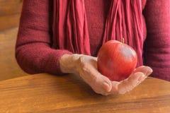 De rode appel in oude handen van bejaarden in rood, sluit omhoog royalty-vrije stock afbeeldingen