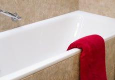 De rode badstofbadhanddoek is op bad met beige tegels royalty-vrije stock afbeelding