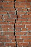De rode bakstenen muur wordt verdeeld door een verticale barst Het concept van de scheiding royalty-vrije stock foto