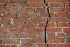 De rode bakstenen muur wordt verdeeld door een verticale barst Het concept van de scheiding royalty-vrije stock afbeeldingen