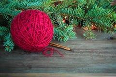 De rode bal van het wolgaren en houten breinaalden dichtbij de groene boom van het Kerstmisbont en heldere kleurrijke lichten op  stock afbeeldingen