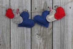 De rode, blauwe en houten harten die van het land op drooglijn met houten achtergrond hangen Royalty-vrije Stock Afbeelding