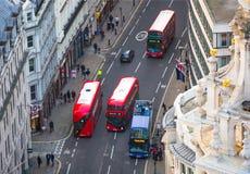 De rode bussen van Londen bij de Stad van de weg van Londen Mening neer van het bureaublok Stock Foto