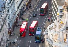 De rode bussen van Londen bij de Stad van de weg van Londen Mening neer van het bureaublok Stock Afbeelding