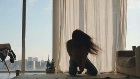 De rode dansen van het haarmeisje in sunlights dichtbij de panoramische vensters stock video