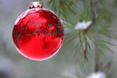 De rode decoratie van Kerstmis op snow-covered pijnboomboom in openlucht Royalty-vrije Stock Foto