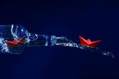 De rode document boten ontsnappen op een waterplons van een fles, donkere blu Stock Foto's