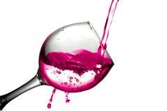De rode droge wijn giet in een wijnglas op een witte achtergrond Stock Foto