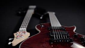 De rode elektrische gitaar en de zwarte baarzen, liggen zij aan zij stock videobeelden