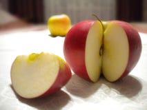 De rode en gele appelen liggen op een wit tafelkleed stock foto