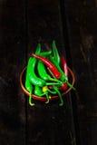 De rode en Groene Hete Houten Lijst van Chili Peppers In Bowl Over Stock Afbeelding