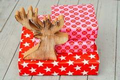 De rode en roze giften van het patroonkerstmis van de sterbloem met houten reindeeron een houten plankenachtergrond Royalty-vrije Stock Fotografie