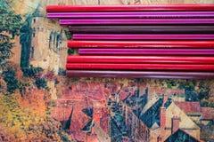 De rode en roze potloden liggen op de reproductie van het kasteel royalty-vrije stock afbeeldingen