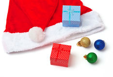 De rode en witte hoed van Santa Claus, stuk speelgoed bellen en Kerstmisgiften Stock Afbeelding