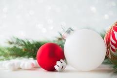 De rode en witte Kerstmisornamenten schitteren vakantieachtergrond Vrolijke Kerstkaart Royalty-vrije Stock Afbeeldingen