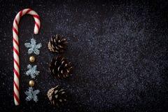 De rode en witte pijnboom van het Kerstmissuikergoed en fonkelende sneeuwvlokken op een zwarte donkere achtergrond Royalty-vrije Stock Afbeeldingen